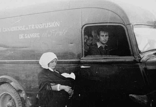 Photo of Hazen Sise driving the Canadian Blood Transfusion Institute van. Behind him in the van are two children. A woman is standing next to the van and holding a baby.