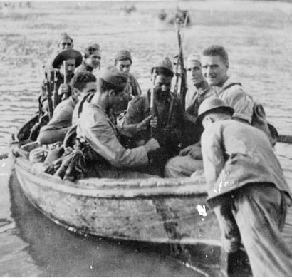 Photo of 9 Mackenzie Papineau volunteers sitting in a boat holding their guns. A man is pushing the boat out into water