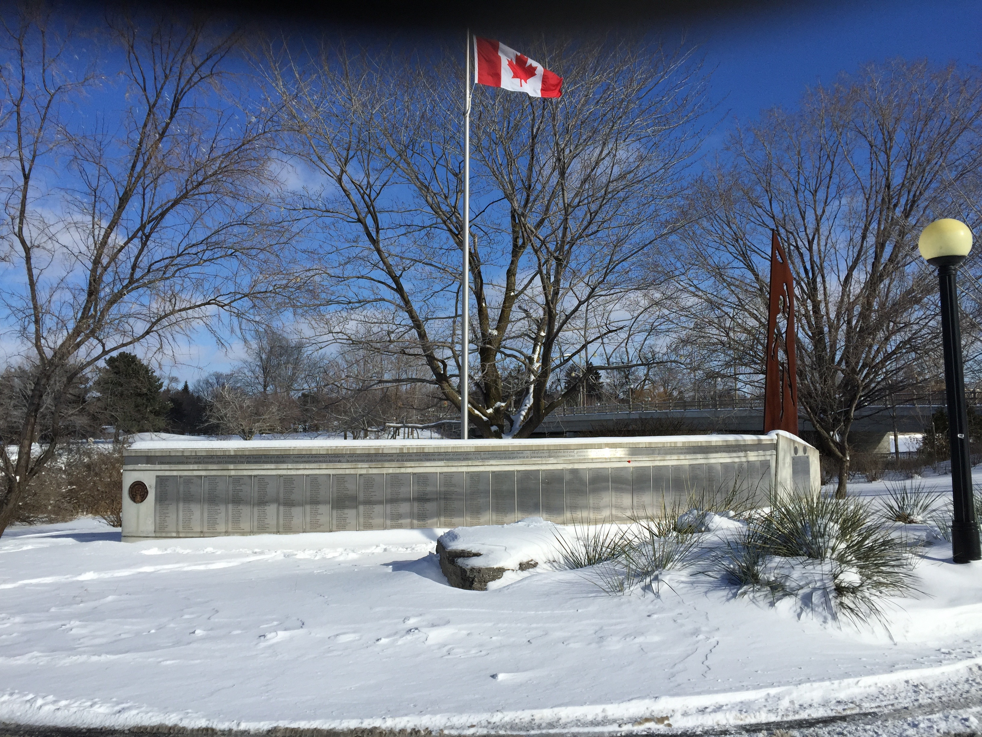 Photo of the Ottawa memorial. A long stone base holds plaques with names of Canadian volunteers. Behind the names stands a Canadian flag.